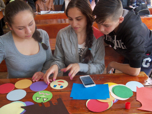 Students create faces displaying different emotions at Avram Iancu Secondary School in Romania