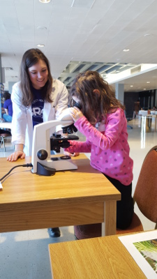 A girl looks through a microscope during B.R.A.I.N. Day organized by Boston University's Mind and Brain Society