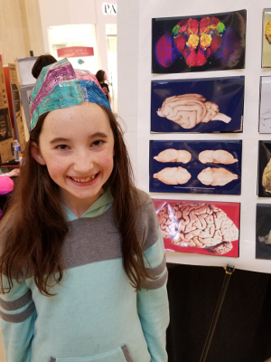 A girl wears a brain hat during an event at the Millcreek Mall organized by Edinboro University of Pennsylvania
