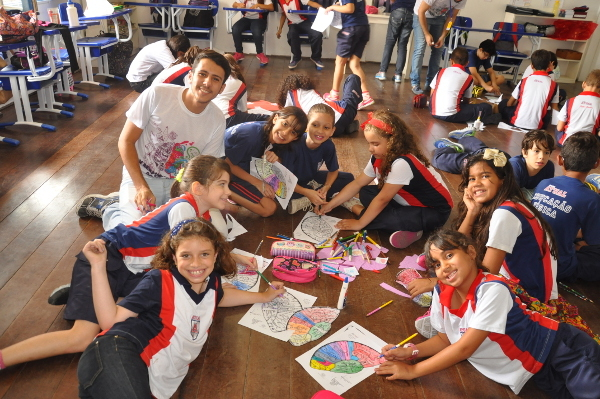 Students color brain diagrams at a school program organized by Faculdade Maurício de Nassau-Caruaru, Brazil