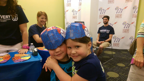BAW coordinators from the Mississippi Chapter Society for Neuroscience look on as kids celebrate their brain hats