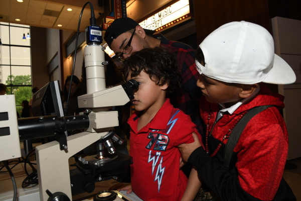 Children look through a microscope during an event organized by the Neuroscience Research Center at The University of Texas Health Science Center at Houston