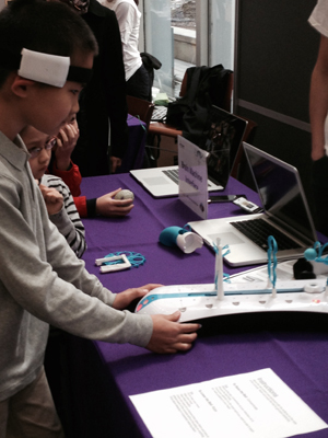 Kids at the New York University Community Brain fair try to move a ball with their brain power with the Mindflex game