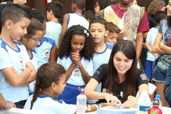 Children learn about electrical stimulation and muscle contraction during an event organized by Universidade Federal de Minas Gerais in Brazil