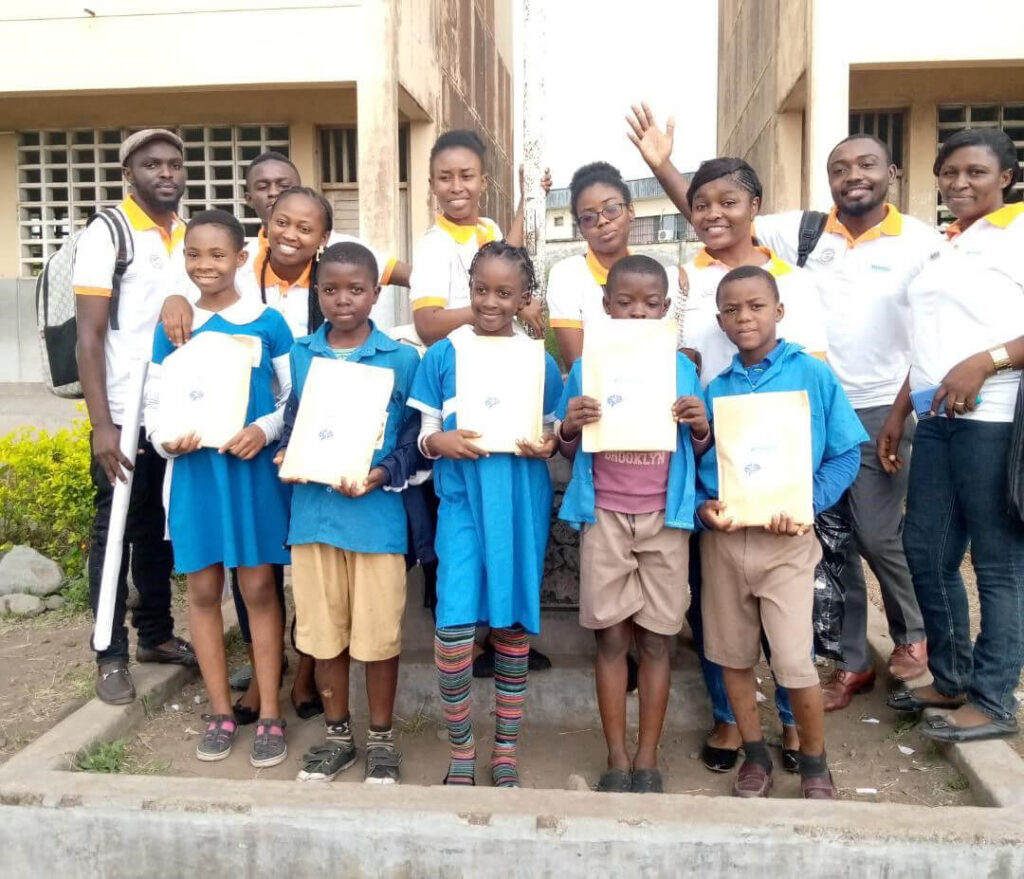 High school students with the best posters stand with younger students for a family photo at an event organized by the University of Buea in Cameroon.
