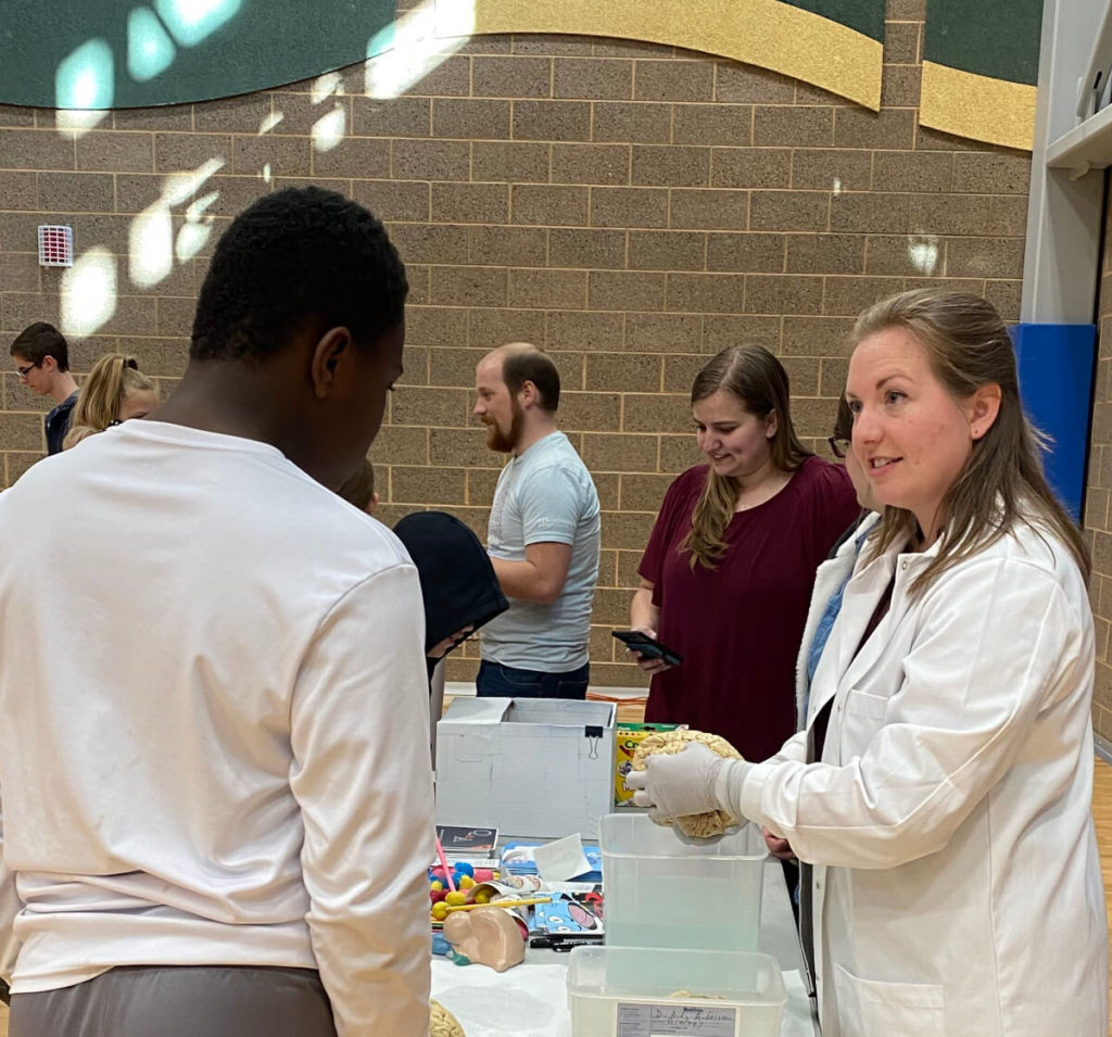 Dr. Sara Freeman showing a human brain to attendees of the STEAM Night event organized by Utah State University.