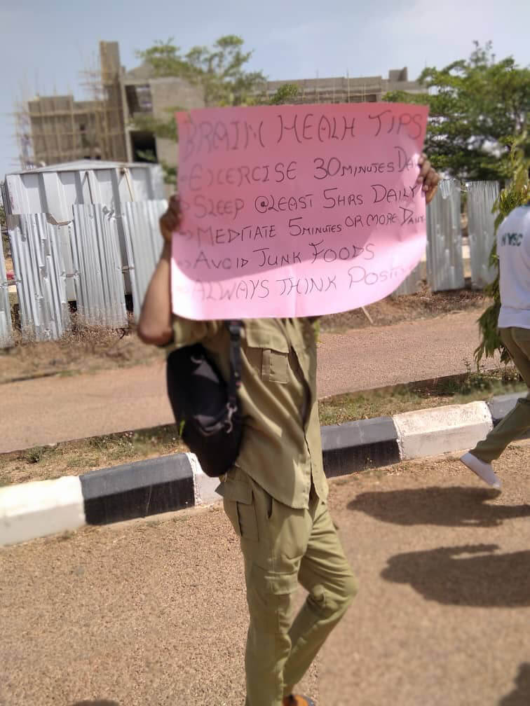 A man holds up a sign advocating for a brain healthy lifestyle, organized by the University of Porthacourt and the Youth Neuroscience Organization Kaduna State in Nigeria, Africa.