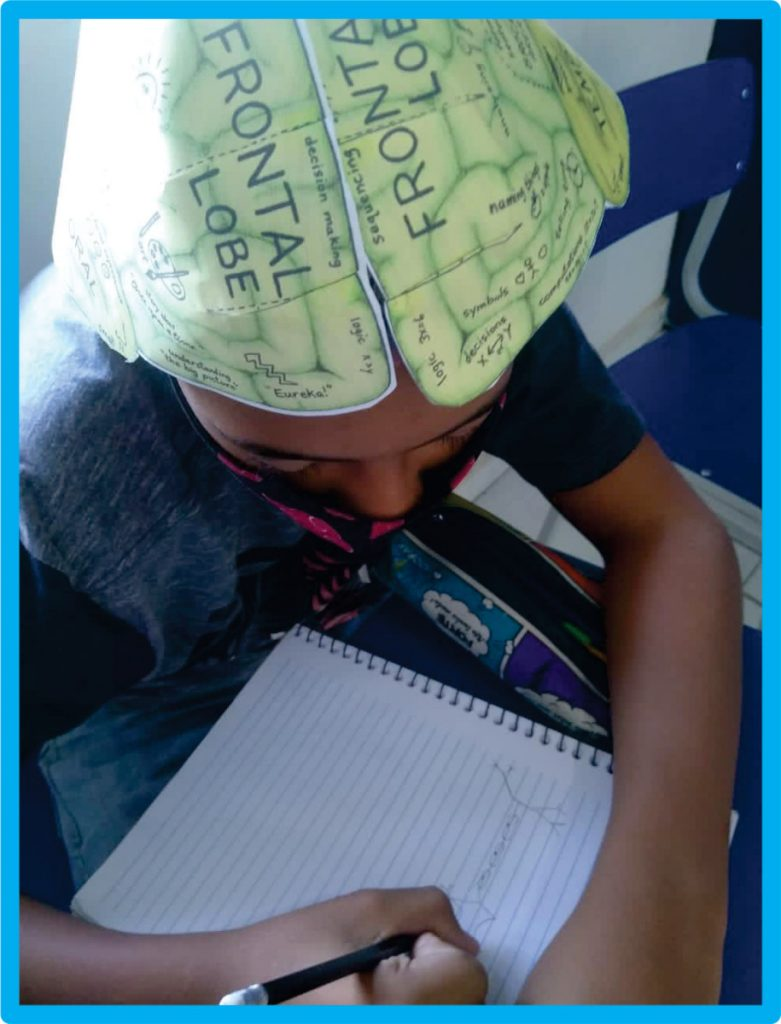 Learning about the brain and wearing a brain hat at an event organized by Centro Educacional Futura in Colombia.