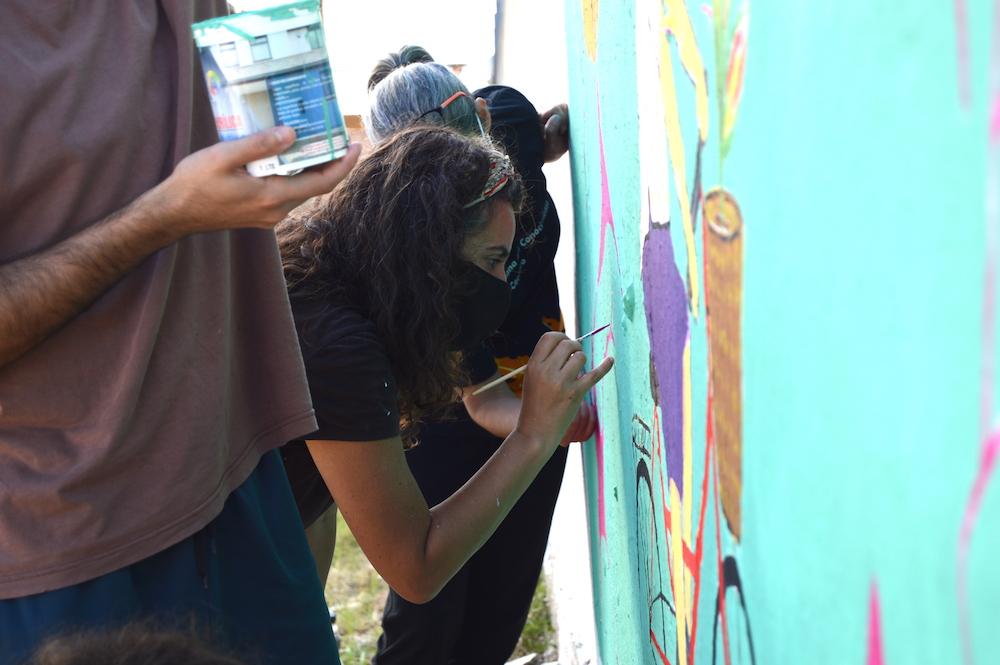 Participants help paint mural at an event organized by the Sociedad de Neurociencias del Uruguay.