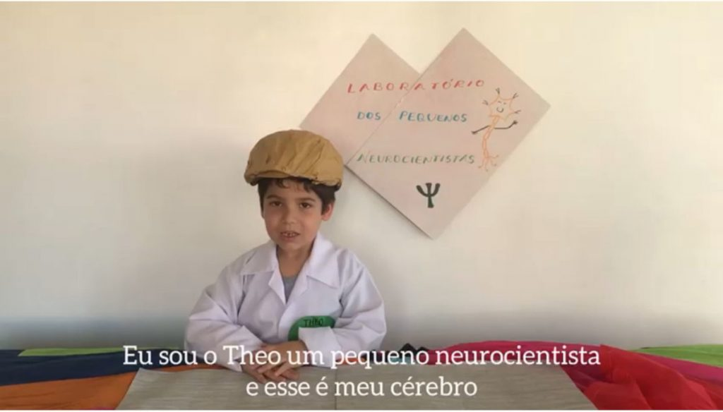 """A """"little neuroscientist"""" in a brain cap presents at a virtual event organized by the University of Fortaleza."""